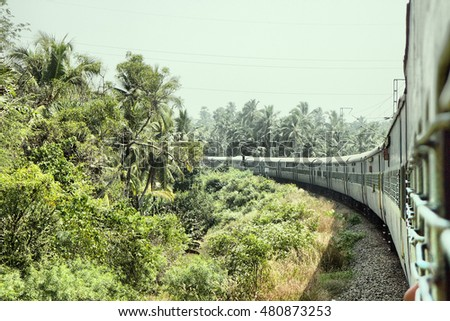 Indian Railways. Railway branch passes through palm forest. Filming trains from window of rear carriage - good example of perspective projection.