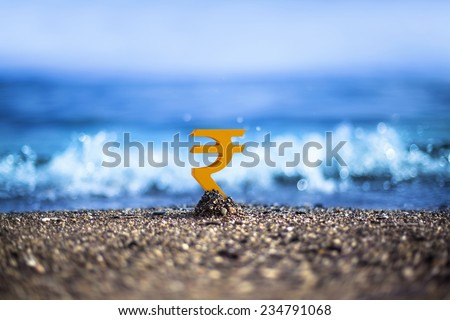 Indian Rupee currency icon is standing on the wavy sea side - stock photo