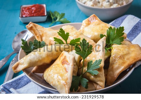 indian samosa filled with chicken curry on tray - stock photo