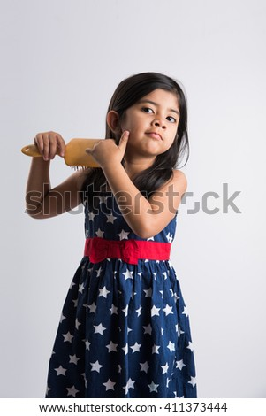 indian small girl combing hair, asian girl with hair brush, small cute indian girl model getting ready with hair brush in hand, small indian girl and hair styling, isolated over white background - stock photo