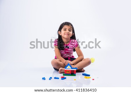 indian small girl or asian girl child playing with colourful blocks over white background, cute little indian girl constructing house with blocks, cute indian girl playing with toys - stock photo