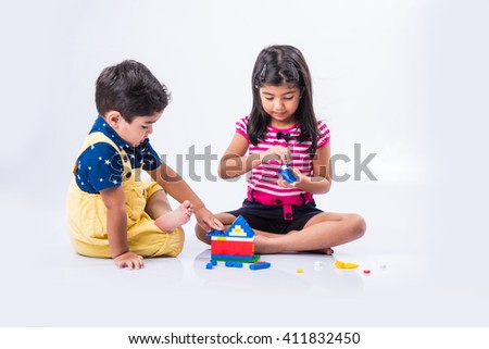 indian small kids or asian brother and sister playing with colorful blocks over white background, cute little indian kids constructing house with blocks, indian kids playing with toys - stock photo