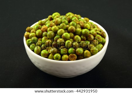 Indian snack: Spiced fried green peas {chatpata matar} in bowl . Selective image photograph, - stock photo