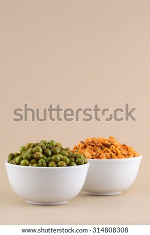 Indian Snacks : Mixture and Spiced fried green peas {chatpata matar} in white bowl. - stock photo