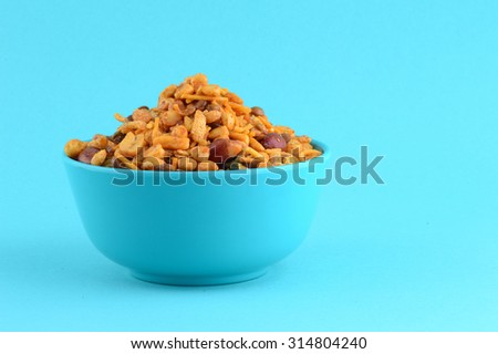 Indian Snacks : Mixture (roasted nuts with salt pepper masala, pulses, channa masala dal green peas) in blue bowl in  - stock photo