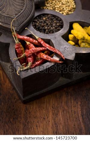 Indian spices | chili, coriander, pepper and turmeric in masala dani, spice box - stock photo