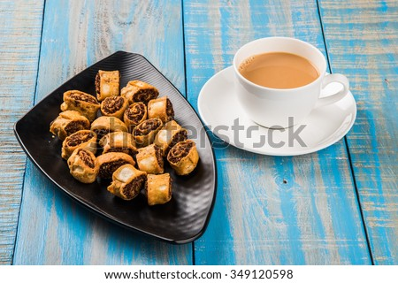 Indian spicy sweet fried snack also known as bakarwadi or bakar wadi served in black plate with tea, favourite snacks of Pune, Maharashtra, Indian snack - stock photo