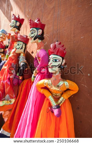 Indian string puppets hanging by a wall. The puppets are used in traditional Rajasthani theatre called Kathputli. - stock photo