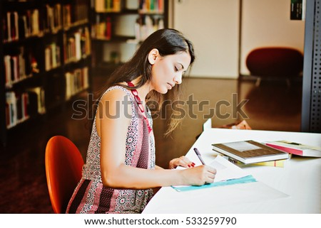 Indian student sitting at the table and writing