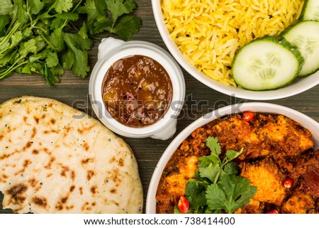Indian Style Chicken Balti Curry With Pillau Rice Naan Bread and Mango Chutney On A Green Wooden Background