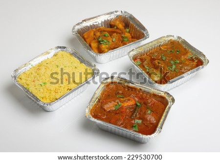 Indian takeaway curry meal in foil containers - stock photo