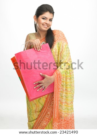 Indian traditional girl with sari carrying pink shopping bags - stock photo