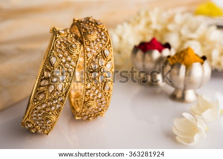 Indian traditional jewellery, bangles with huldi kumkum and white flowers - stock photo