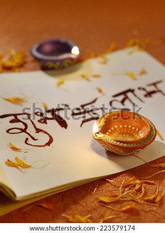 Indian traditional lamps placed on a book with Sanskrit calligraphy - stock photo