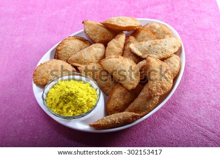 Indian traditional Snack Gujiya served in plate along with Holi color in a bowl