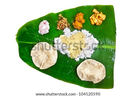 Indian traditional vegetarian thali from rice, dal, potatoes, tomato salad and two puri on banana leaf isolated on white background. Free space for text - stock photo