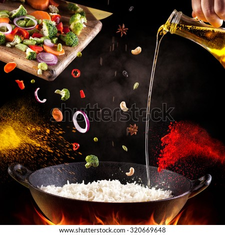 Indian vegetarian biryani with vegetables and spices in cooking process on black background - stock photo