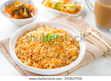 Indian vegetarian food. Biryani rice, curry dhal and milk tea on dining table.  - stock photo