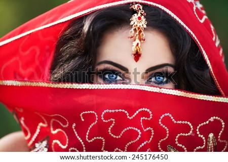 Indian woman bride, beautiful indian girl traditional sari costume covered face with veil, India. Girl bollywood dancer in Sari. Arabian bellydancer. Indian wedding makeup - stock photo