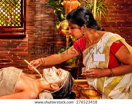 Indian woman does facial mask at ayurveda spa. - stock photo
