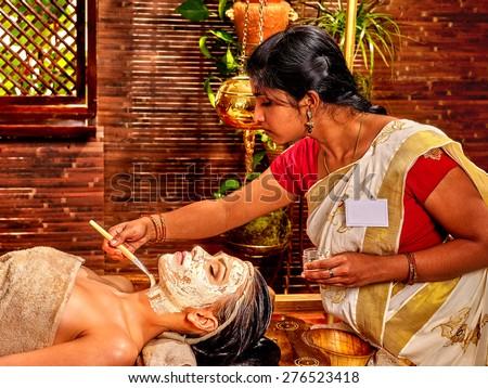 Indian woman does facial mask at ayurveda spa. - stock photo