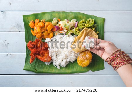 Indian woman eating banana leaf rice, overhead view on wooden dining table. - stock photo