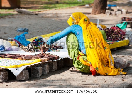 Indian woman in colorful sari sells souvenirs, bangles and cheap jewelry at street market place. Fort Cochin (Kochin),  Kerala, India - stock photo