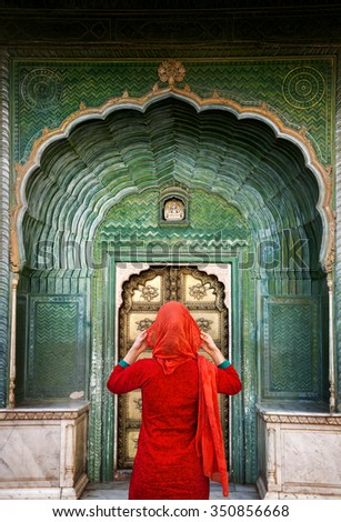Indian Woman in red scarf looking at green gate door in City Palace of Jaipur, Rajasthan, India. Space for your text, can be used as book or magazine cover. - stock photo