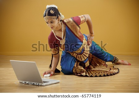 Indian woman in traditional dress using a laptop - stock photo