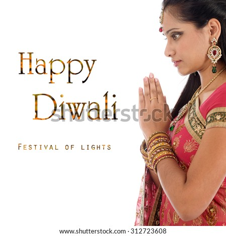 Indian woman in traditional sari praying and celebrating Diwali or deepavali, fesitval of lights at temple. Girl prayer hands folded, isolated on white background. - stock photo