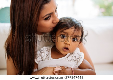 Indian woman kissing her adorable baby girl - stock photo