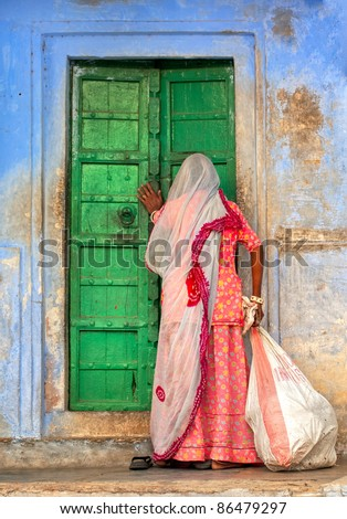 Indian woman knocking on the door - stock photo
