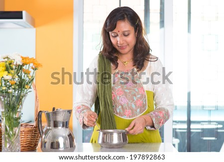 Indian woman preparing meal inside kitchen. Asian female cooking food at home.