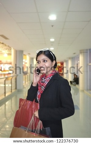 Indian Woman talking on phone in a mall. - stock photo