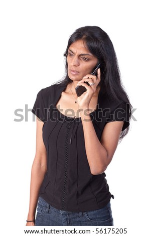 Indian woman, with a serious look, listening to a cellphone - stock photo