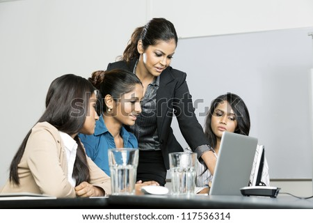 Indian women business colleagues working around a laptop - stock photo