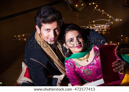 Indian young and handsome husband gifting necklace to his beautiful wife on the occasion of Diwali or anniversary, happiness concept, selective focus