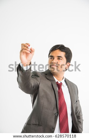 indian young businessman writing in the air with marker pen, isolated over white background
