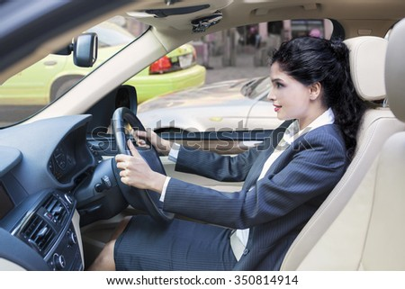 Indian young businesswoman wearing formal suit and driving her car - stock photo