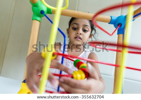 Indian Young girl play with the wooden bead wire - stock photo