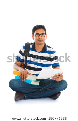 indian young male student surfing while sitting on the floor