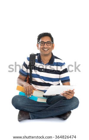 indian young male student surfing while sitting on the floor - stock photo