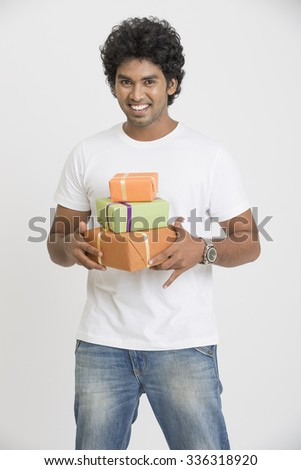 Indian young man holding gift boxes on white. - stock photo