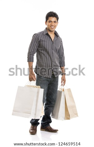 Indian young man with shopping bags on white background.