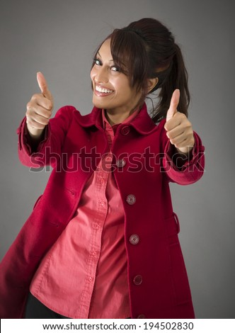 Indian young woman making thumbs up sign from both hands - stock photo