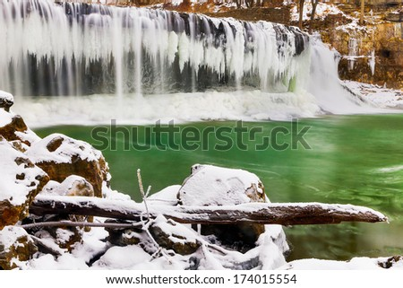 Indiana's Upper Cataract Falls is adorned with icicles in a snowy landscape. - stock photo