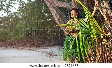 Indigene woman in the palm skirt on the tropical forest background - stock photo