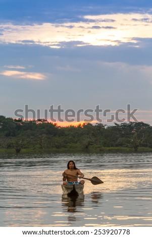 Indigenous adult man with canoe on Laguna Grande, Cuyabeno national park, Ecuador at sunset, model released - stock photo
