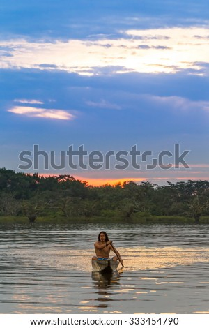 Indigenous Adult Man With Canoe On Laguna Grande Cuyabeno National Park Ecuador At Sunset Model Released - stock photo