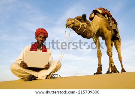 Indigenous Indian man with his laptop out in a desert. - stock photo